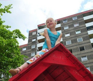 Kind sitzt auf Spielhausdach im Hintergrund ist die Wohnanlage zu sehen