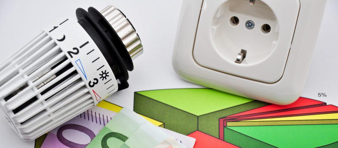 Steckdose, Heizungsregler und Geld als Symbol für Betriebskosten