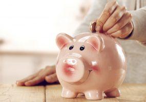 Sparschwein wird mit Geld für Kaution befüllt