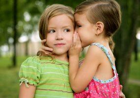 Mädchen flüstert anderem Mädchen ins Ohr