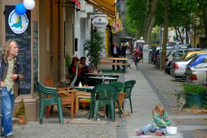 Der Klausernplatz in Berlin. Auf dem Boden ist ein junges Mädchen zusehen, dass mit Kreide malt. Von links kommt ein älterer Mann.