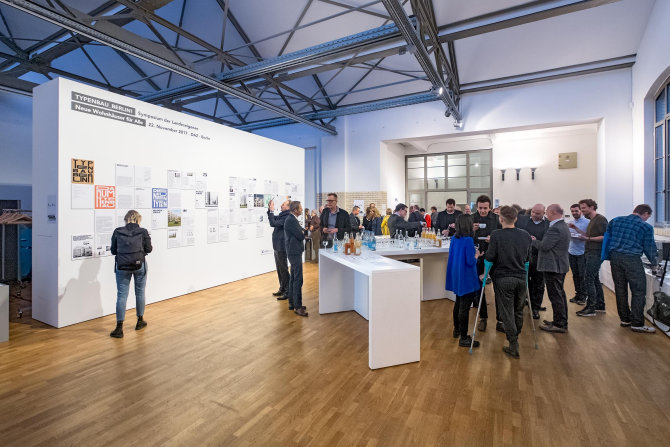 Eine Ansammlung von Menschen im Symposium Typenbau Berlin.