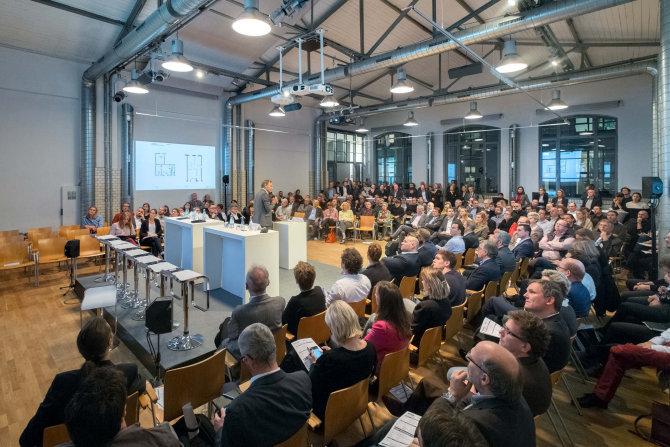 Mehrere Menschen sitzen in einem Raum und hören einem Sprecher zu.
