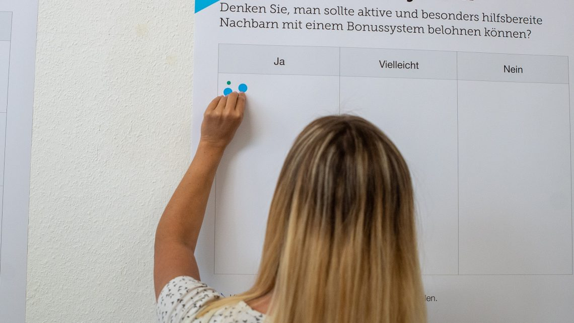 Eine blonde Frau klebt Aufkleber auf ein Poster der Gewobag.