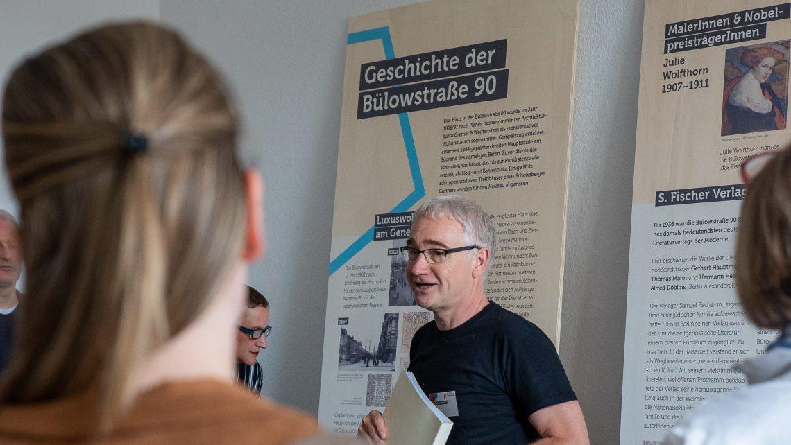 Ein grauhaariger Mann steht vor Infoplakaten der Geschichte der Bülowstraße 90.