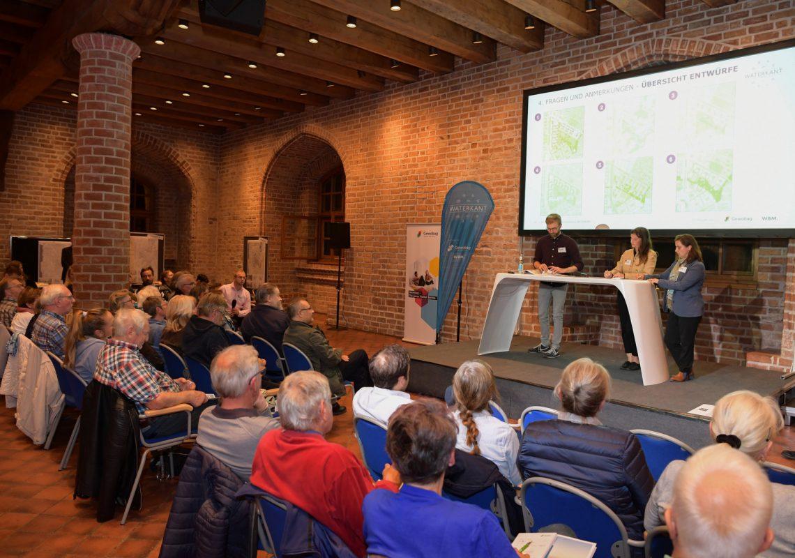 Bürgerveranstaltung zur Waterkant. Drei Leute stehen vor einem Projektor. Im Publikum sitzen mehrere, hauptsächlich ältere Menschen.