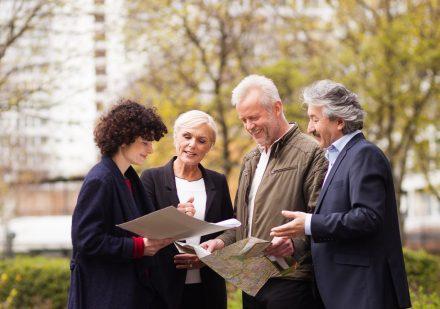 Mehrere Menschen stehen in einem Wohnpark und schauen auf eine Karte.
