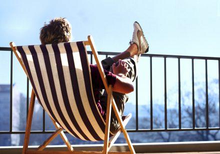 Ein junger Mann sitzt in einem Klappstuhl und hebt die Beine entspannt hoch.