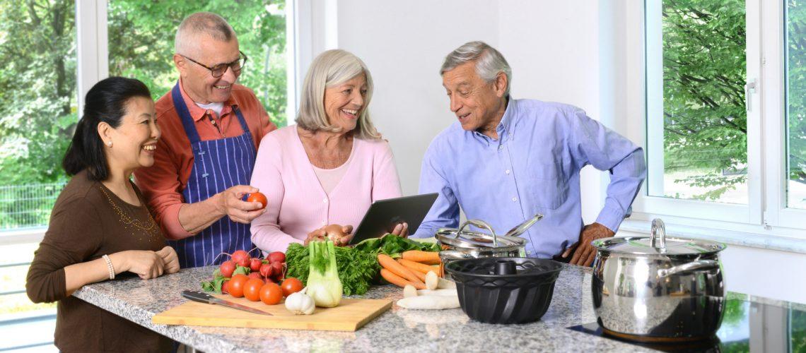 Vier Rentner stehen gemeinsam in der Küche und kochen.