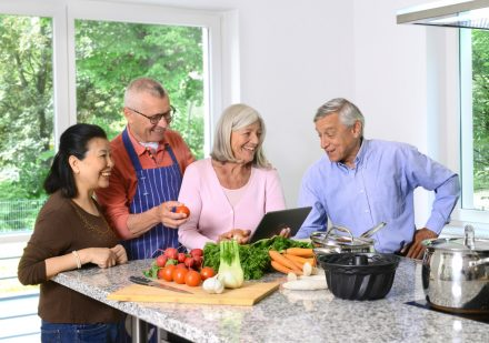 Vier Menschen stehen gemeinsam in der Küche und kochen.