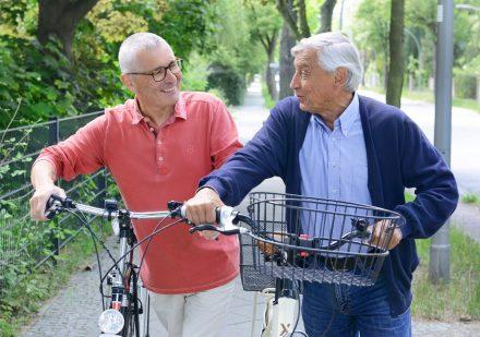 Zwei grauhaarige Herren mit einem Fahrrad.