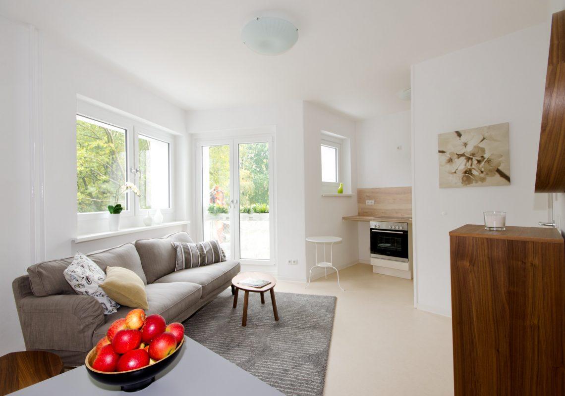 Eine Neubauwohnung mit hellen Wänden und einem Balkon. Es ist eine Couch und Äpfel zu sehen.