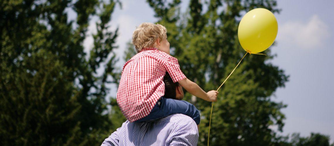 Kind mit Luftballon Huckepack