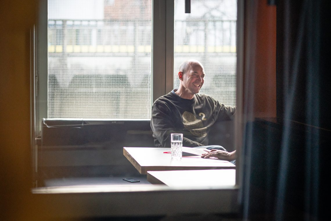 Mann sitzt an einem Tisch vor einem Fenster.
