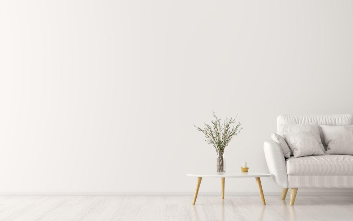 Weiße Couch, weißer Tisch mit Tischpflanze in einem weißen Raum.