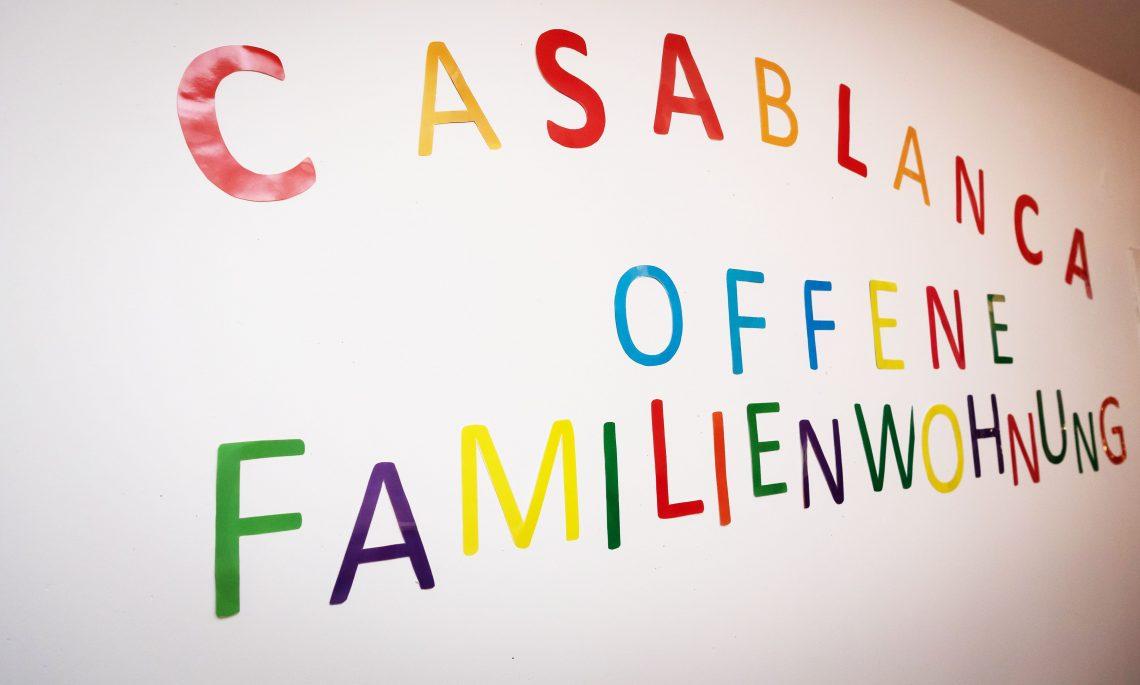 """Der Schriftzug """"Casablanca. Offene Familienwohnung"""" in bunten Buchstaben an der Wand"""
