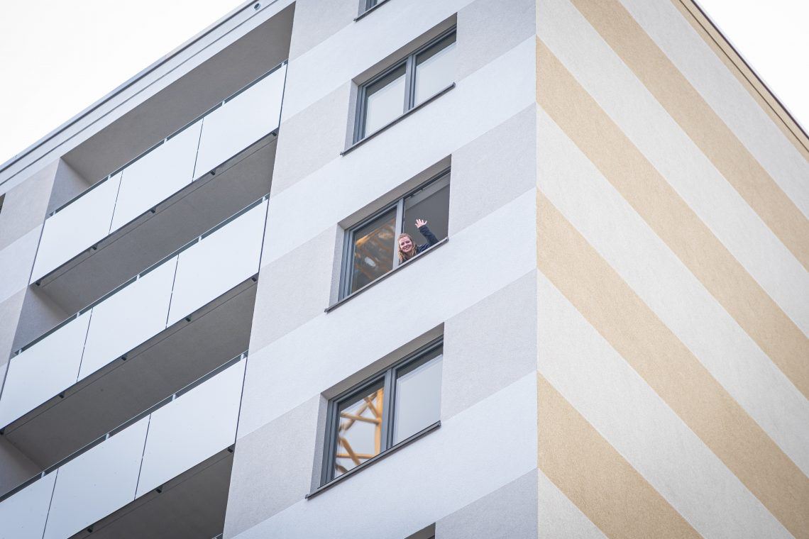 A young woman waves from the window of a skyscraper.