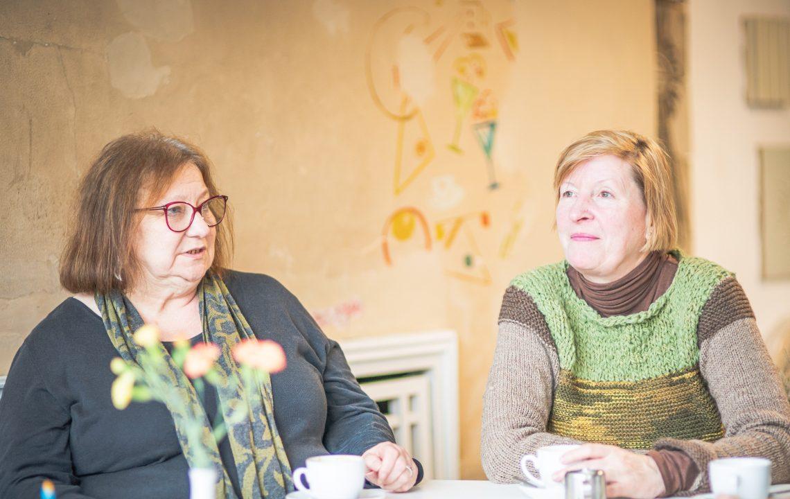 Zwei Frauen sitzen am Tisch und trinken Kaffee.
