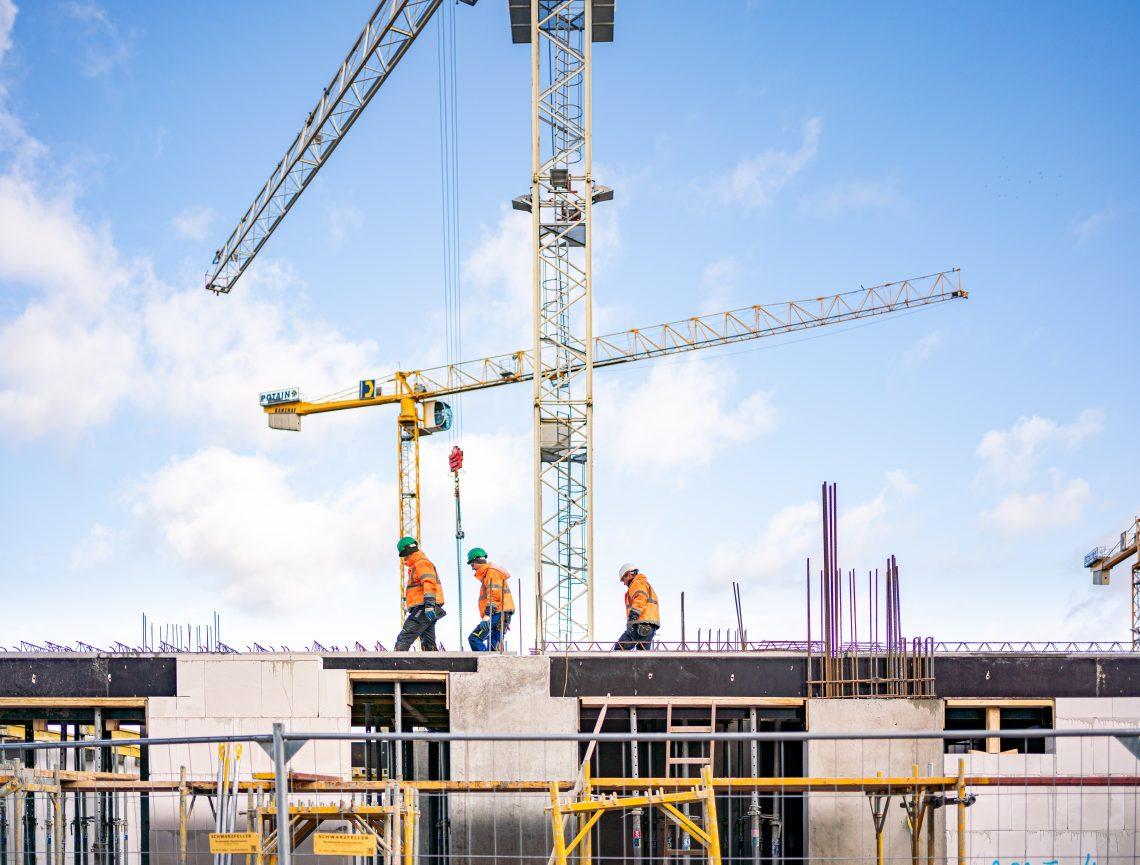 Bauarbeiter vor Baukränen auf einem Rohbau des Bauprojektes WATERKANT Berlin