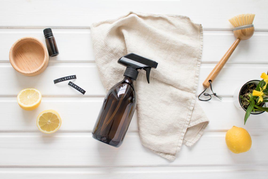 Bildcollage mit Sprühflasche, Öl, Zitronen, Handtuch und Bürste.