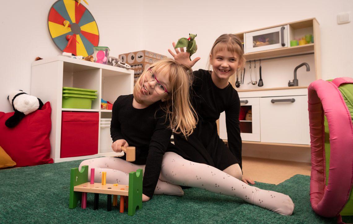 Zwei Mädchen spielen in der offenen Familienwohnung auf dem Boden.