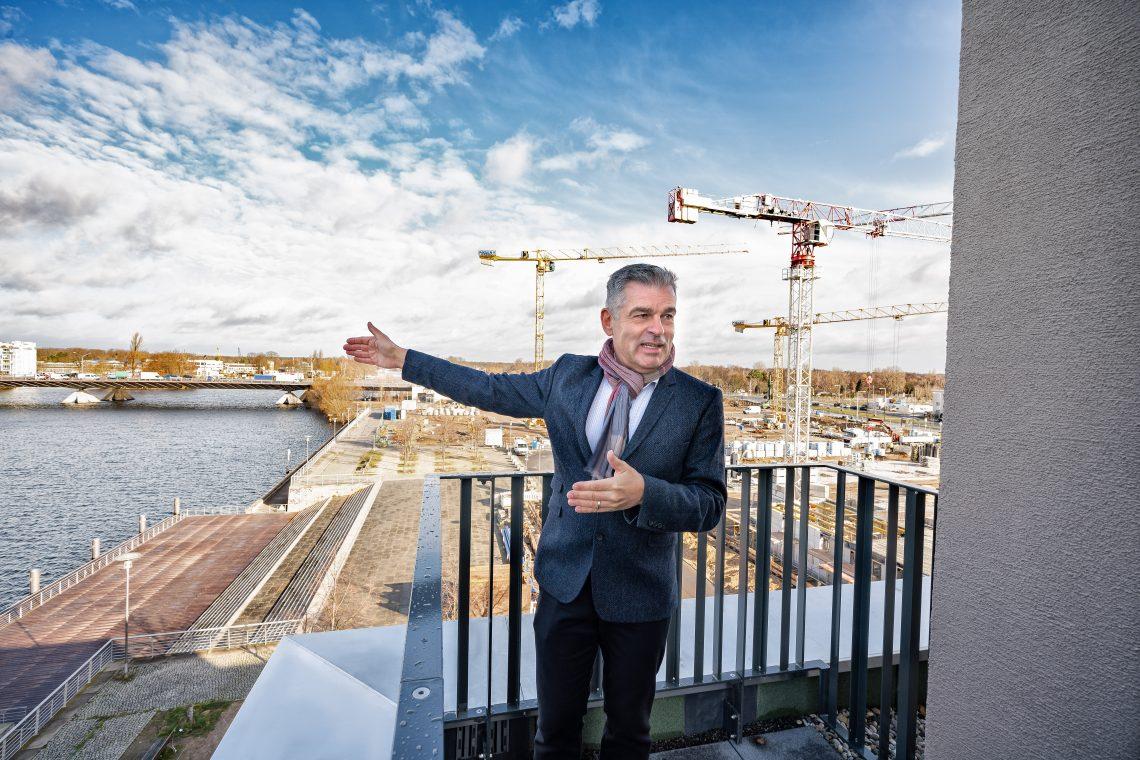 Peter Ehrlich auf der Terrasse einer fertigestellten Wohnung vom Teilprojekt 1