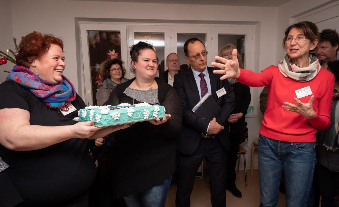 Eine Menschengruppe feiert die Einweihung der zweiten offenen Familienwohnung mit Kuchen.