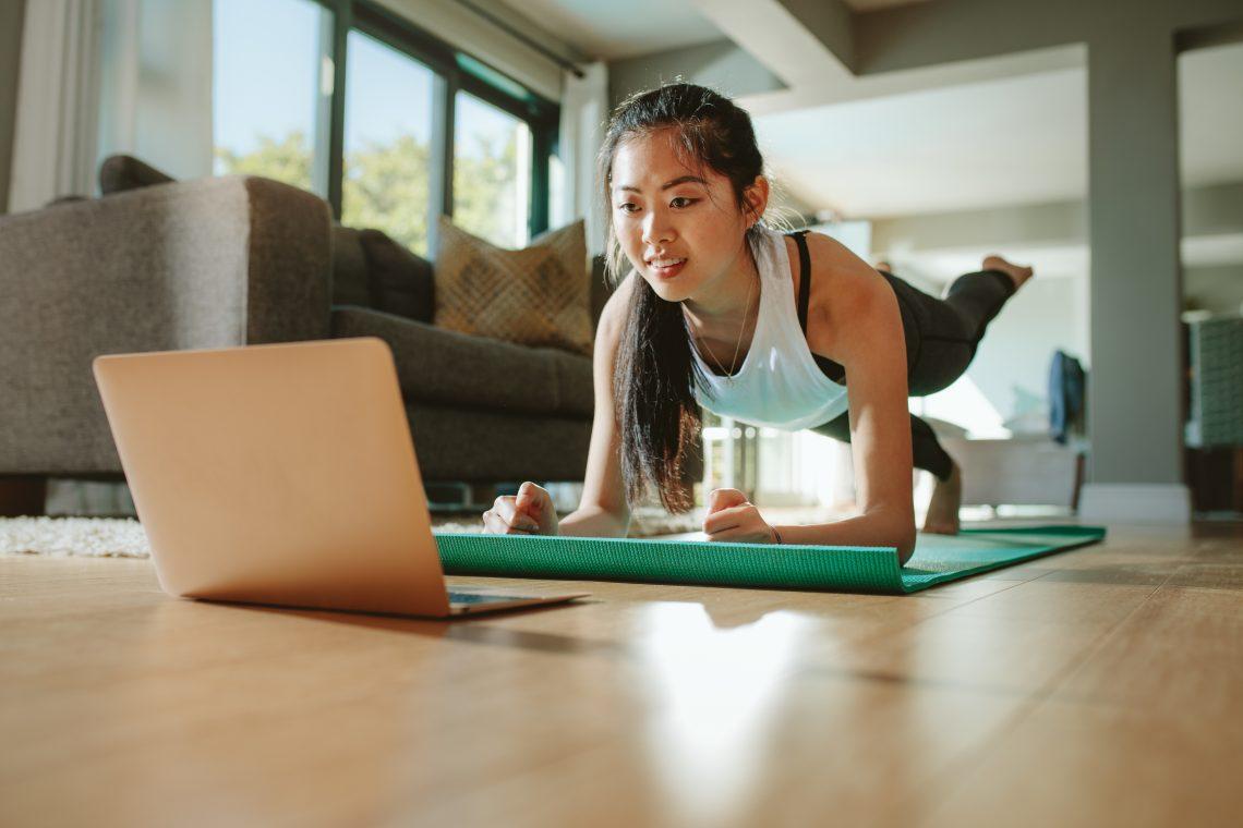 Frau macht vor einem Laptop Sport.
