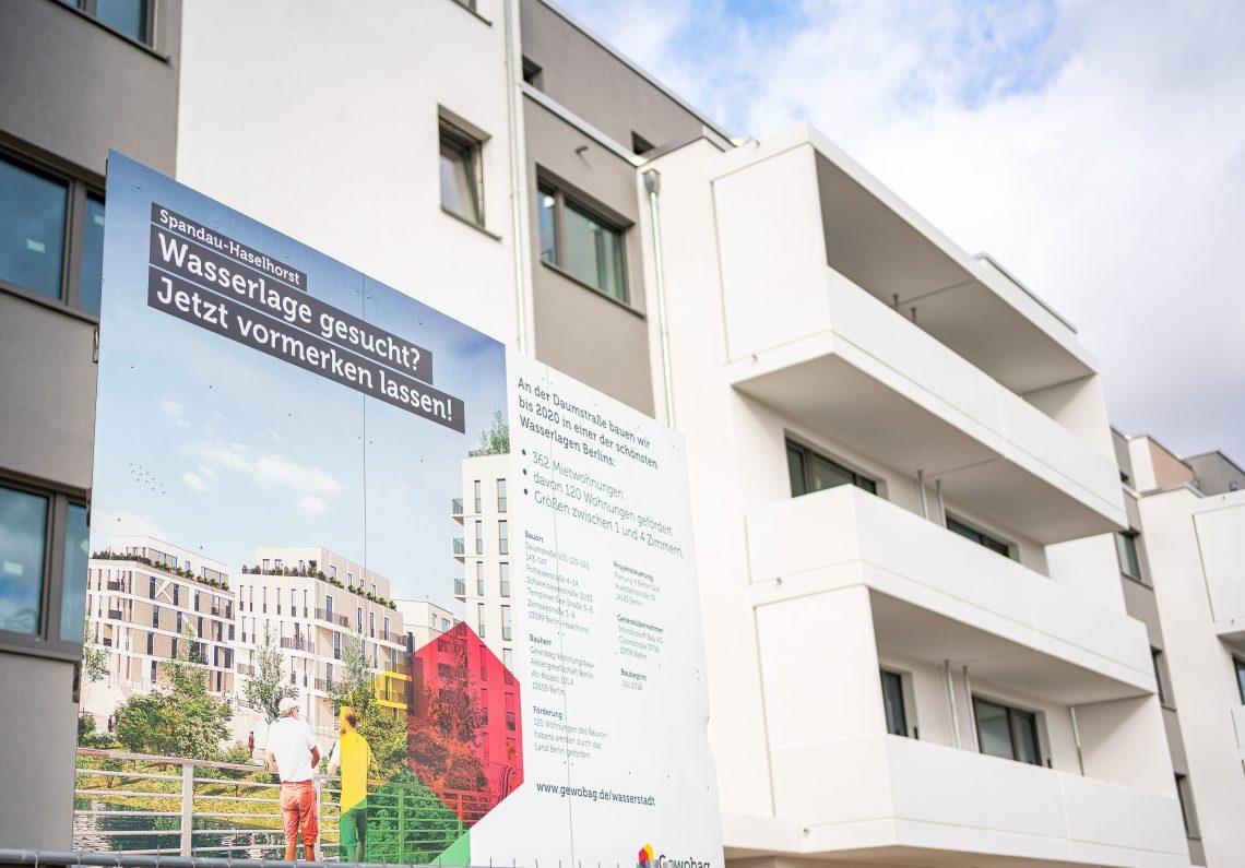 Bauschild vor fertiggestelltem Haus von Teilprojekt 1