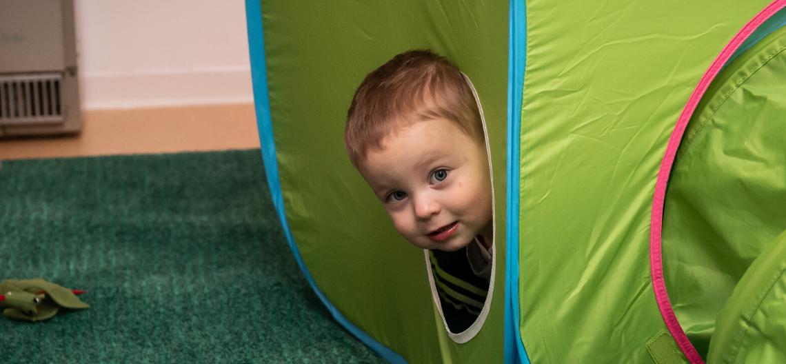 Kind steckt Kopf aus einen Spielwürfel