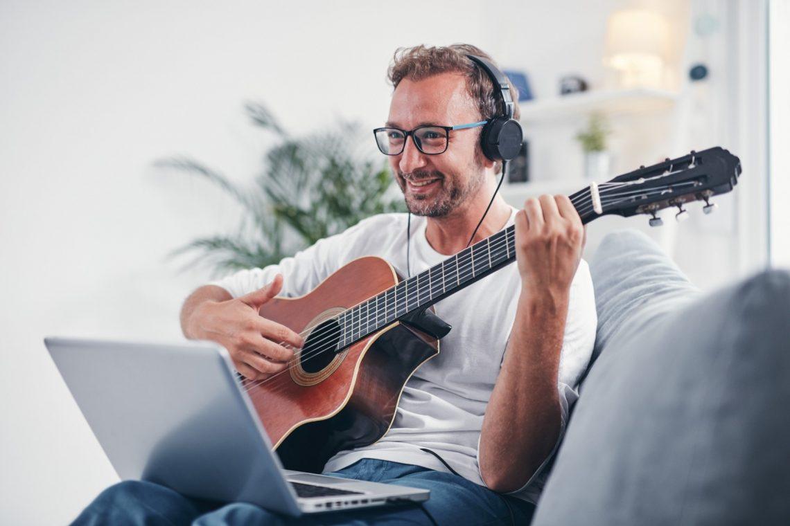Mann sitzt auf dem Sofa und spielt vor einem Laptop Gitarre.