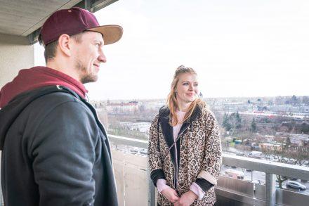 Junges Paar auf dem Balkon seiner Wohnung.