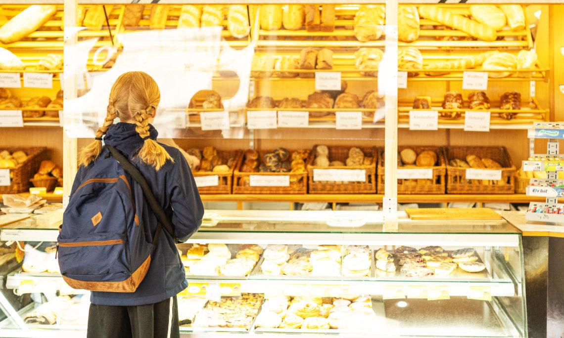 Mädchen mit Schulranzen in der Bäckerei Rajemann.