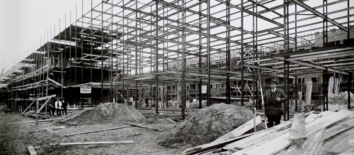 Ein altes Schwarz-Weiß-Bild. Ein mann steht vor einem Baugerüst und trägt einen schwarzen Anzug.