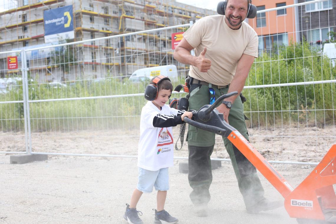 Kind unterstützt Bauarbeiter mit schwerem Gerät