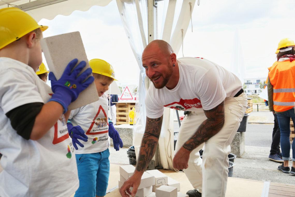 Kinder bauen Mauer beim Tag der kleinen Baumeister