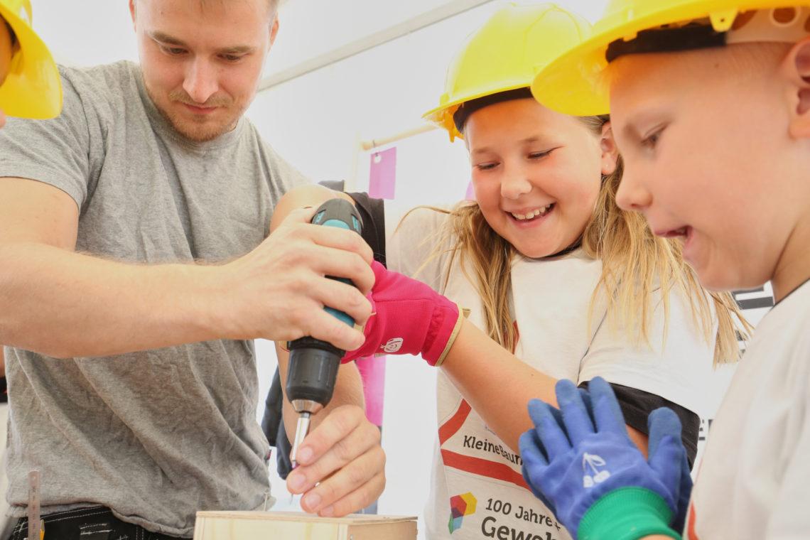 Kinder bohren beim Tag der kleinen Baumeister