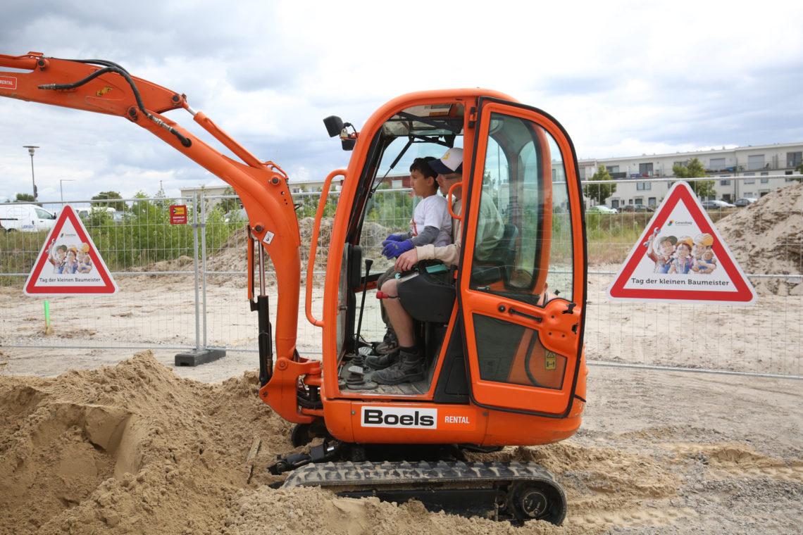 Kind sitzt beim Tag der kleinen Baumeister im Bagger