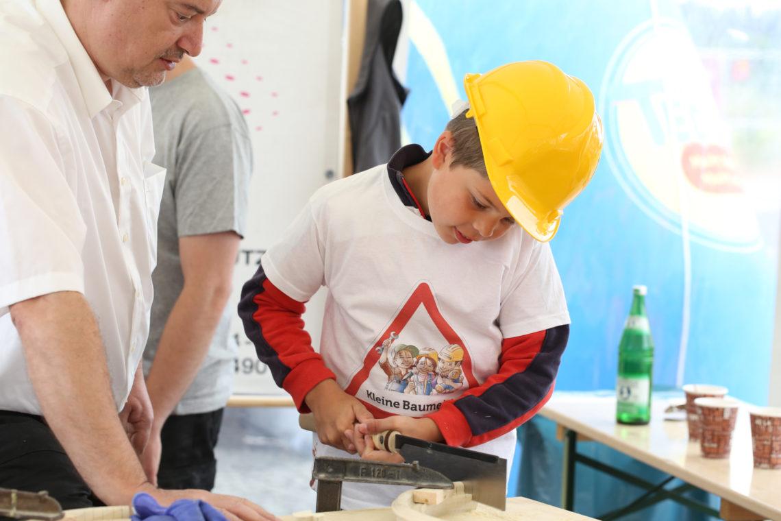 Kind sägt beim Tag der kleinen Baumeister
