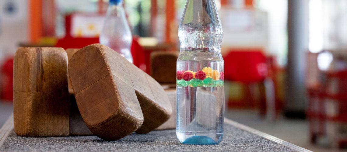 Holzklötzer liegen neben einer Wasserflasche im Extavium