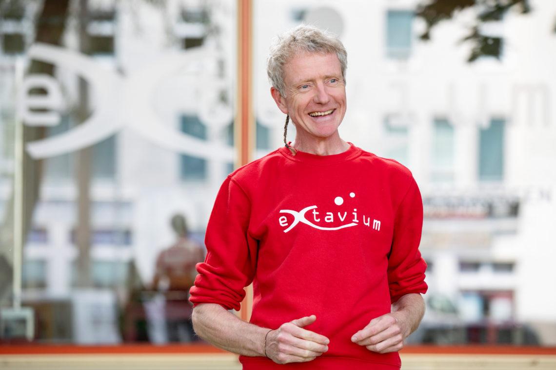 """Dr. Axel Werner trägt einen roten Pullover mit der Aufschrift """"extavium"""" und hält einen Vortrag."""