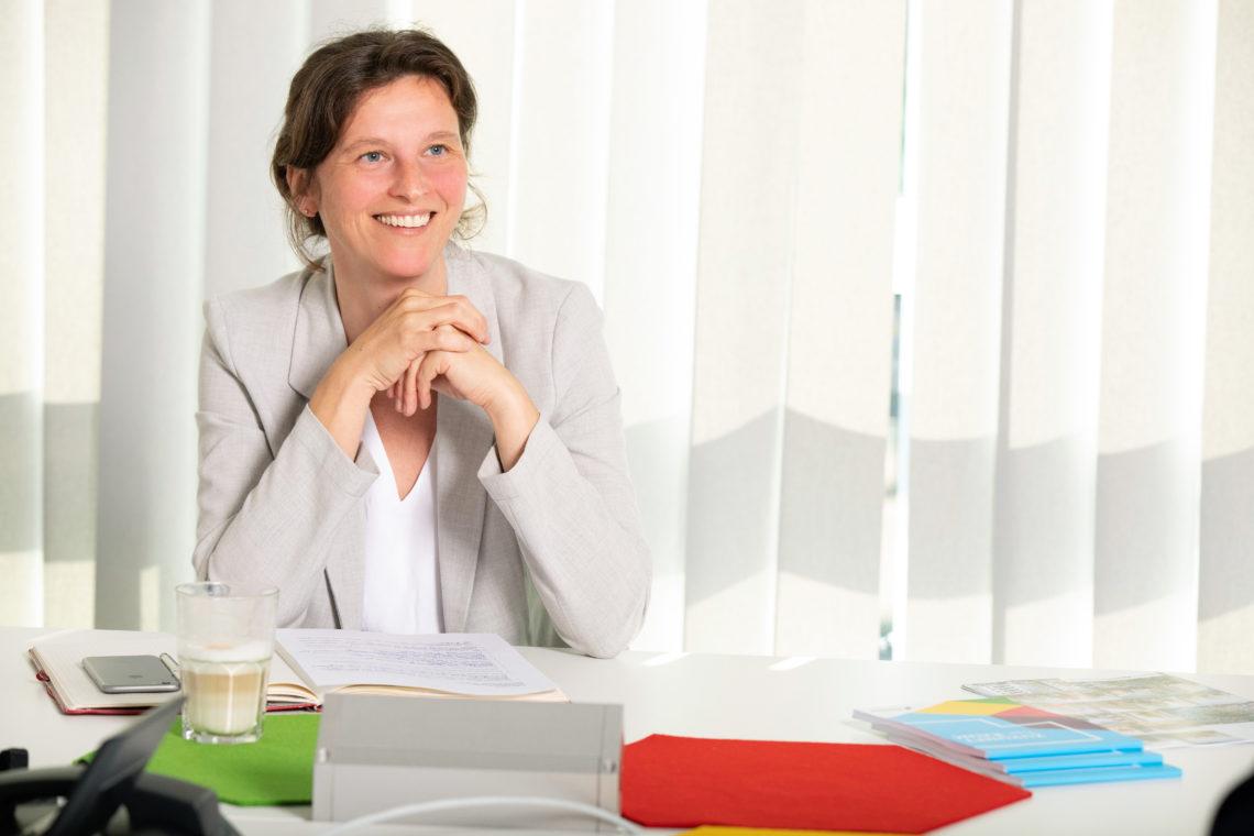 Nancy Baltruschat sitzt lächelnd am Schreibtisch vor Unterlagen zu Neubauprojekten.