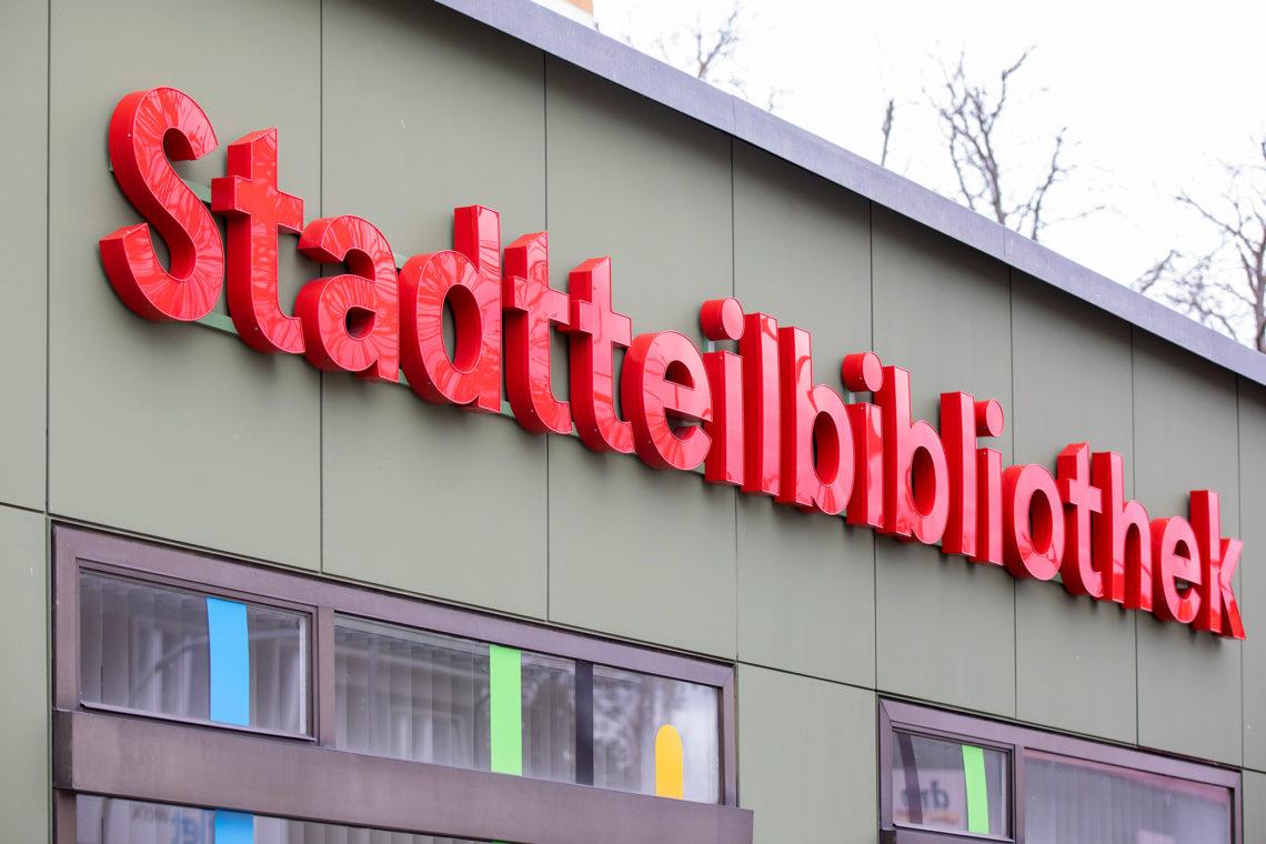 """Rote Schriftzug """"Stadtteilbibliothek"""" auf grauer Hausfassade"""