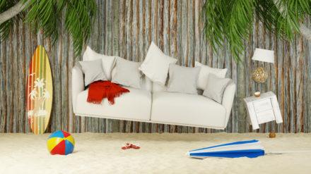 Ein weißes Sofa schwebt umgeben von einem Surfbrett und einem Wasserball an einem Strand.