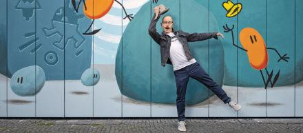Mann steht vor einem Gemälde vom Urban Nation Museum