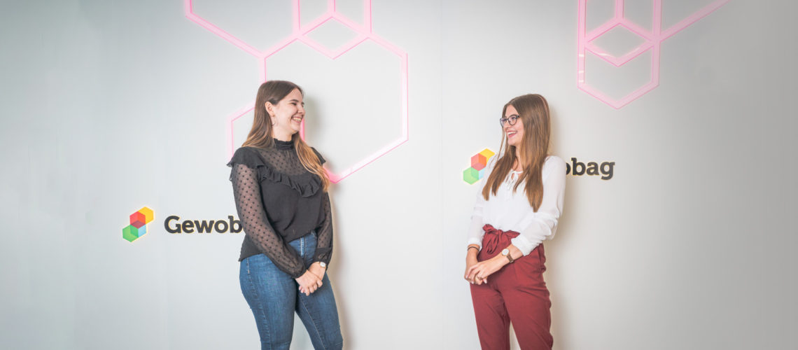 Zwei Frauen stehen vor Logo der Gewobag
