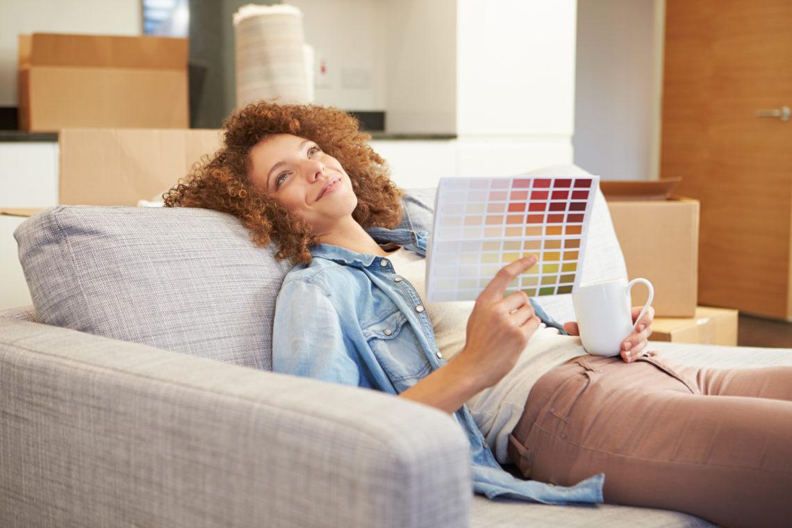 Eine Frau Schaut sich eine Farbkarte an.