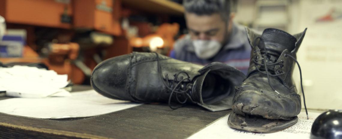 Schuhe im Vordergrund, Schuster Ibrahim Contur im Hintergrund
