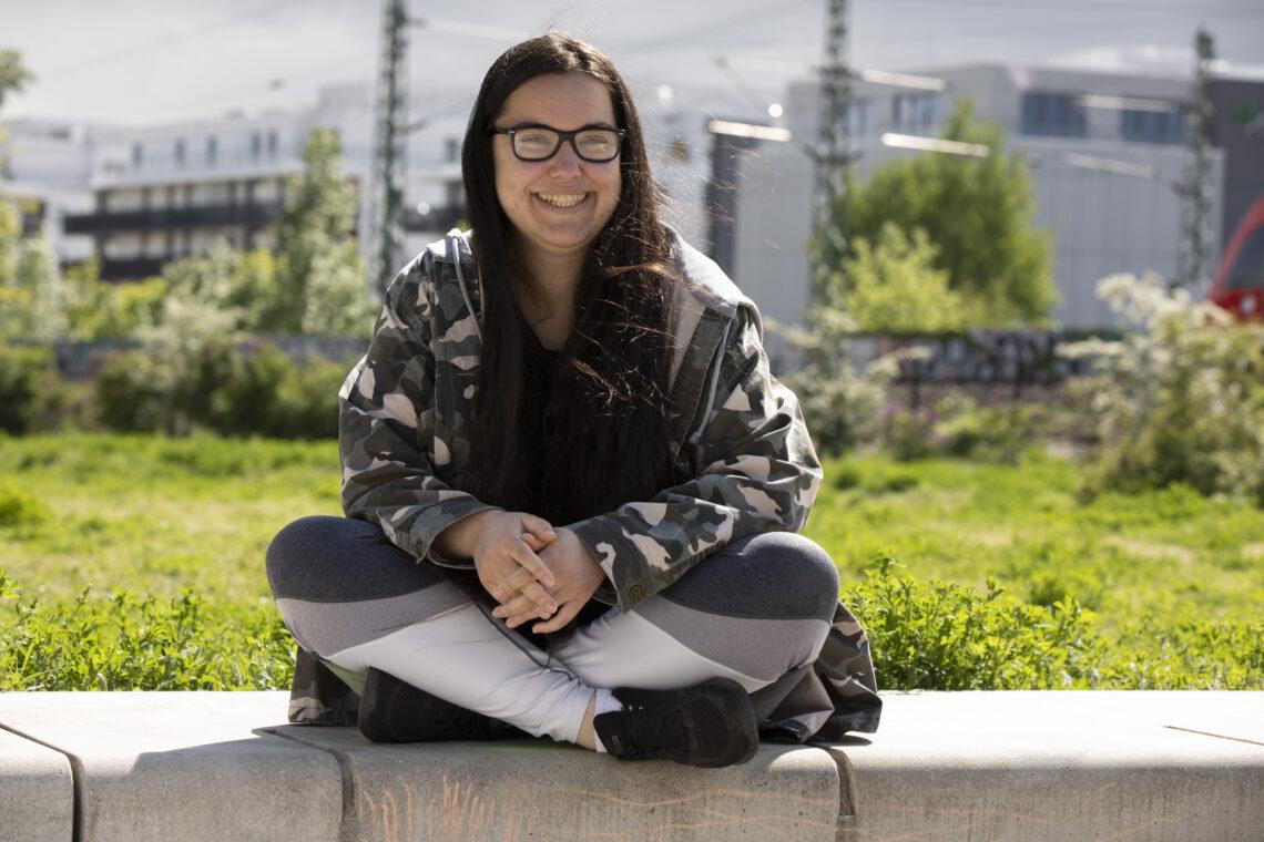 Eine Joblinge-Teilnehmerin sitzt auf einem Stein.