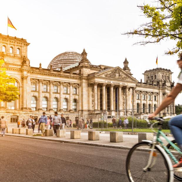 Frau fährt Fahrrad vor dem Reichstag